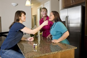 Three women standing around a kitchen counter smelling a bottle of Joy essential oil.