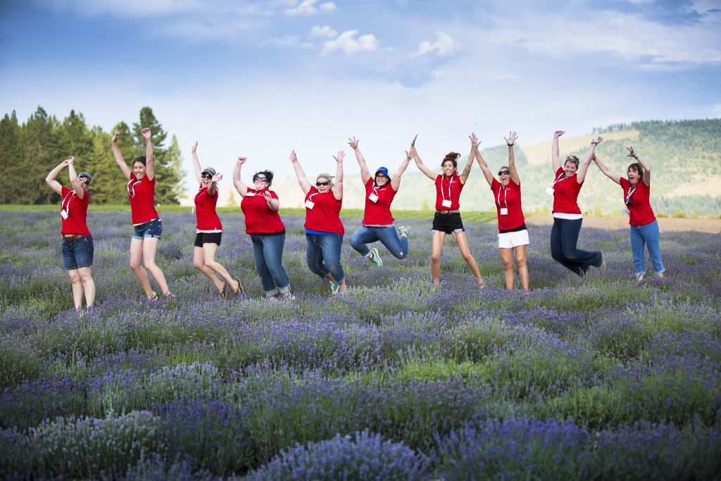Seven women in red t-shirts jumping in a lavender field.