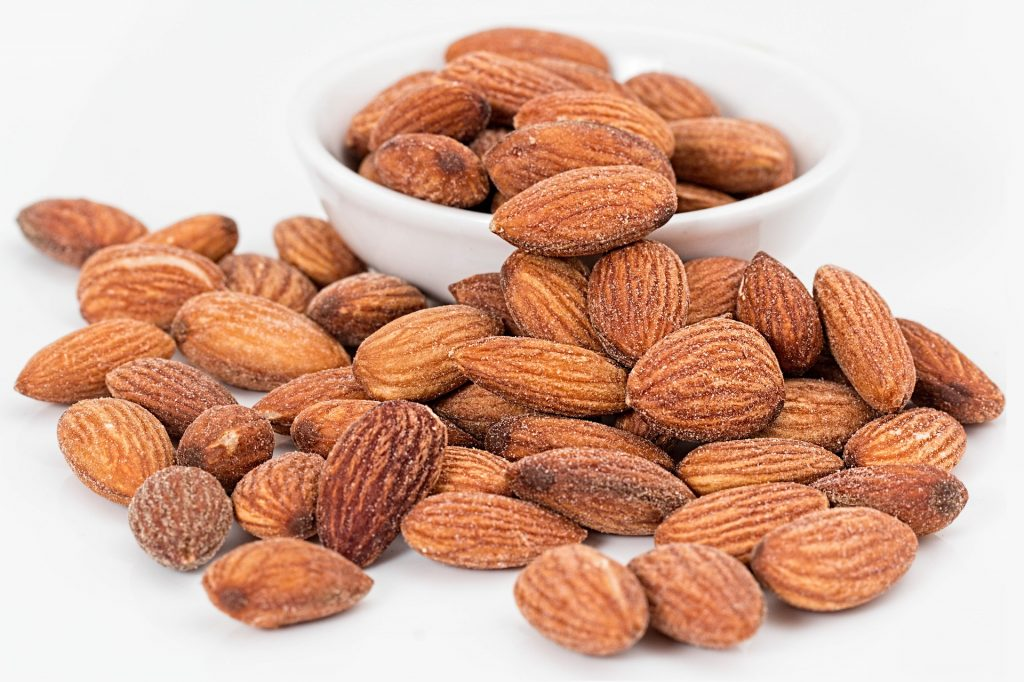 A close-up of almonds in a small bowl and piling onto a white countertop.