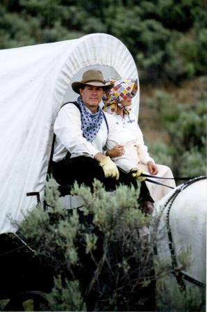 Gary Young and Mary Young in covered wagon celebrating Pioneer Day