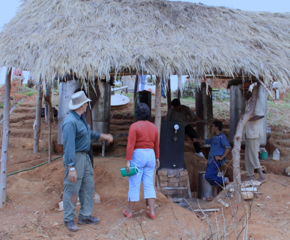 Gary teaches a woman in Madagascar the correct procedures for distilling vetiver essential oil.