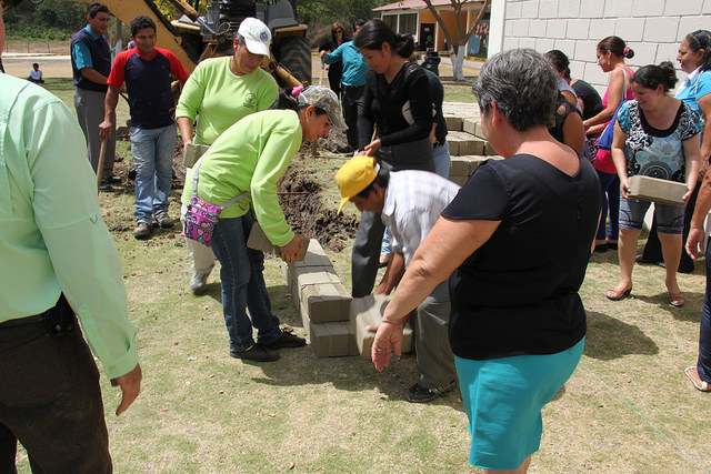 The parents of children in Gary Young's Chongon, Ecuador, school lay the first bricks for the expansion of the school to include high school students.