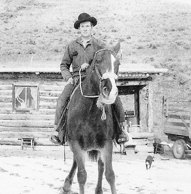 Gary's father, Donald N. Young, on horseback in front of the family's one-room cabin with a dirt roof.