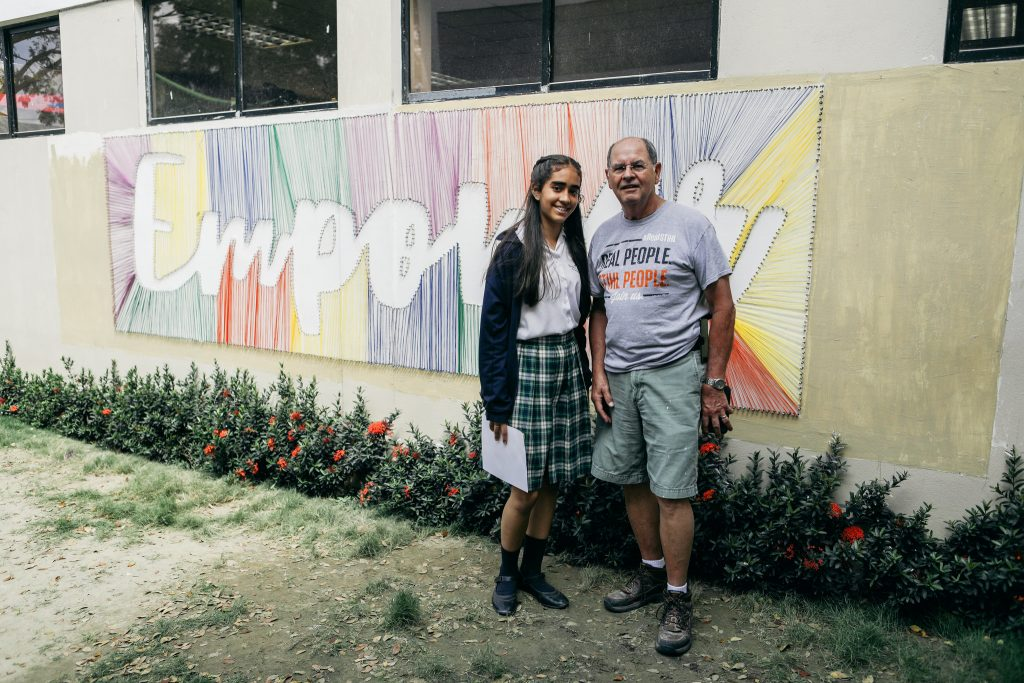 "Two people, a young woman and an older man, stand in front of a wall decorated with the word ""empower."""