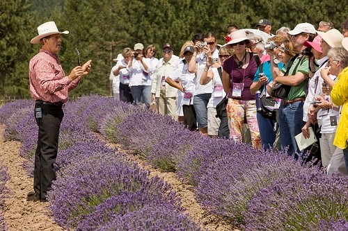 D. Gary Young teaching people, in a field of lavender, how to find the best essential oils.